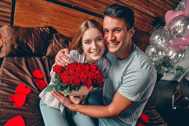 남자는 여자에게 빨간 장미 꽃다발을 준다. 부부가 하트 모양의 색종이를 들고 침대에 앉아 있습니다.