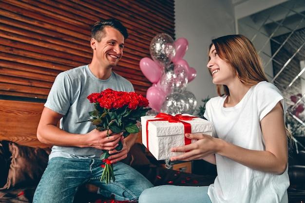 男性は女性に贈り物と赤いバラを贈ります。カップルがハート型の紙吹雪を持ってベッドに座っています。