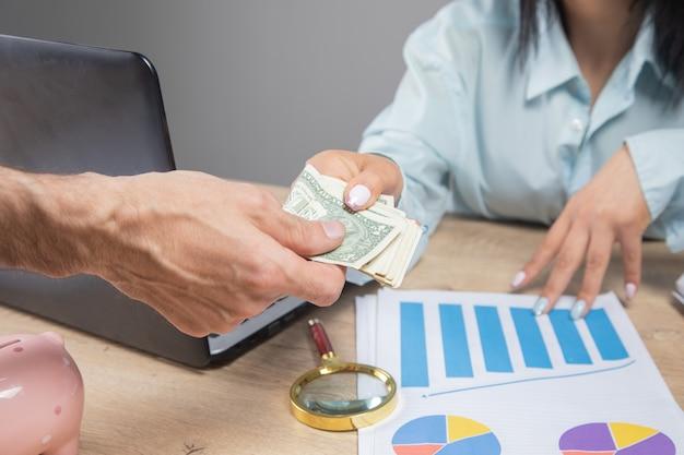 한 남자가 책상에서 여자에게 돈을 준다