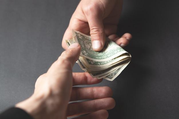 黒いシーンで男が別の男にお金を与える