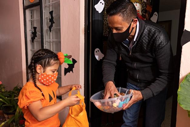 Мужчина дарит конфеты девушке в костюме тыквы в ночь на хэллоуин