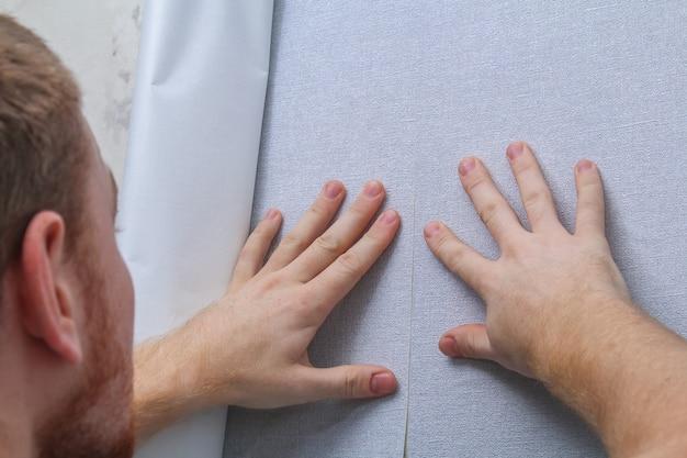 한 남자가 부직포 뒷면에 회색 비닐 벽지를 붙입니다. 방의 리노베이션.