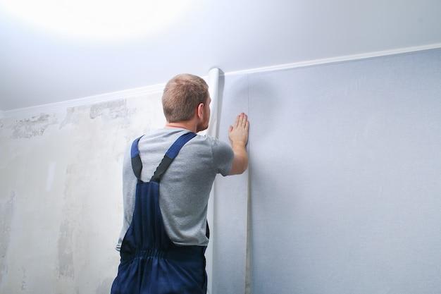 Мужчина клеит серые виниловые обои на флизелиновой основе. ремонт комнаты.