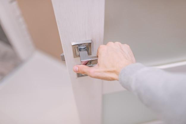 한 남자가 손으로 문 손잡이를 잡고 문을 열어 방으로 들어갑니다.