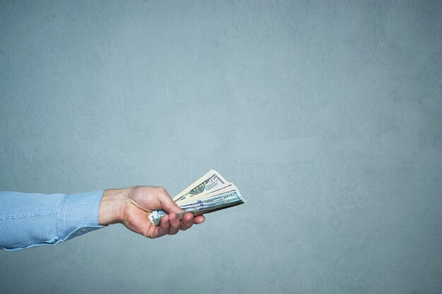 お金のクローズアップを与える男の手。ビジネスと投資の概念