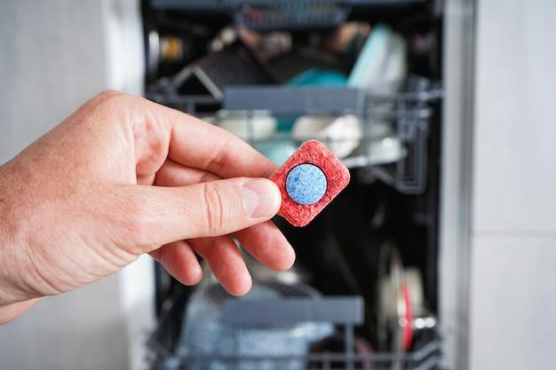 食器洗い機用洗剤のタブレットを持っている男の手。