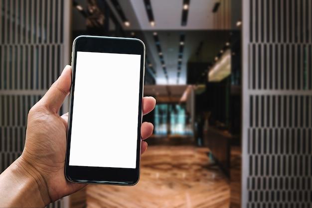 明るいオフィスの部屋のインテリアでスマートフォンデバイスを持っている男の手。