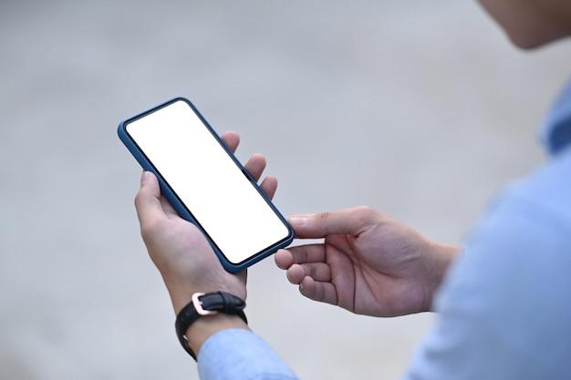 Мужчина вручает смартфон с пустым экраном для текстового сообщения или информационного содержания.
