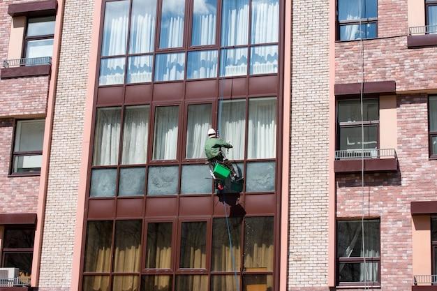 밧줄에 매달린 남자가 창문을 닦는다.