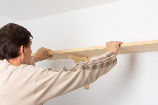 한 남자가 아파트의 흰 벽에 선반을 걸고, 작업자가 선반의 균일성을 확인합니다.
