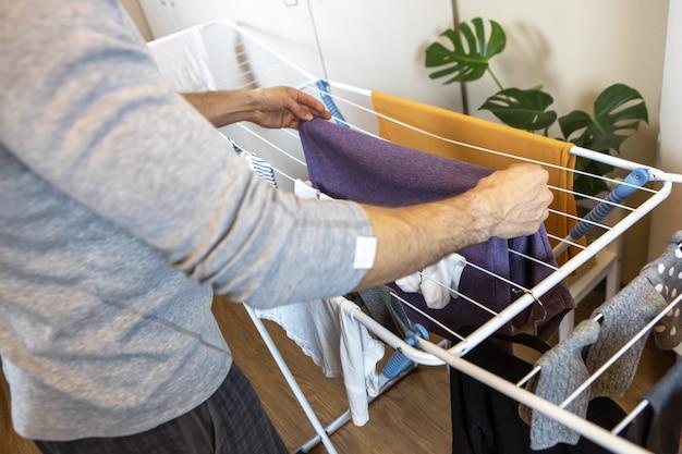 Мужчина вешает выстиранную одежду на сушилку, которая находится в одной из комнат квартиры. концепция гигиены, помощь мужчинам женщинам по дому, смена ролей, ежедневная уборка. по горизонтали.