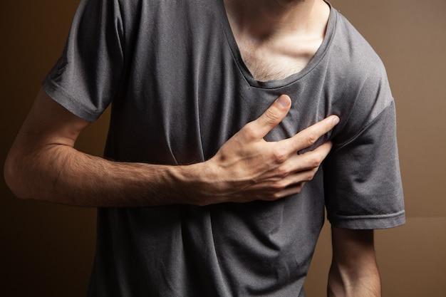 У мужчины болит сердце на коричневом фоне