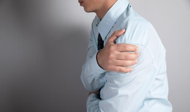 男性は灰色の表面に肩の痛みがあります