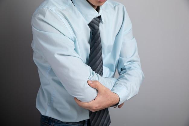 У мужчины болит локоть на серой поверхности