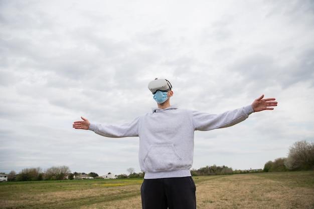 屋外のフィールドでバーチャル リアリティ ヘッドセットを使って楽しんでいる男性。