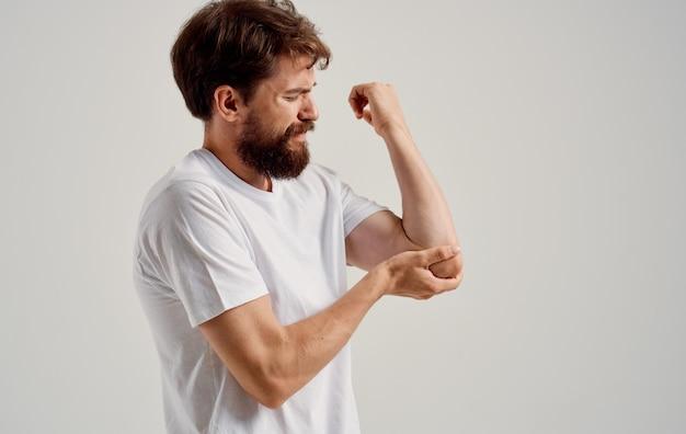 한 남자가 손 손목 팔꿈치 근육 위축에 통증이 있습니다.