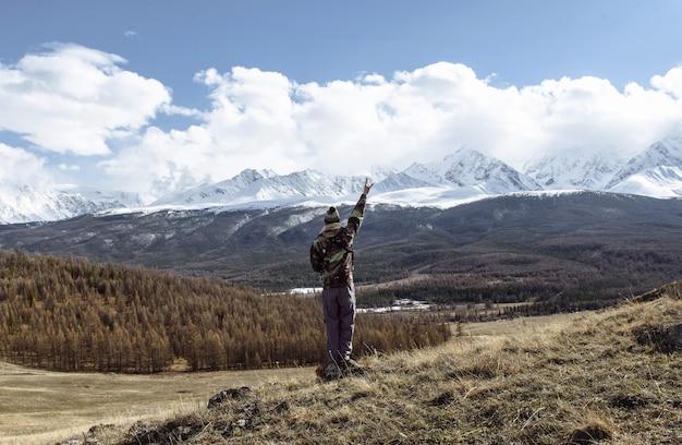 한 남자 등산객이 승자의 포즈로 손을 들고 눈 덮인 산을 바라보고 로큰롤 기호를 보여줍니다. 관광 및 여행 개념