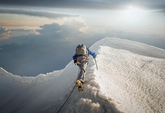 Мужчина, идущий в одиночку на вершине медленной горы.