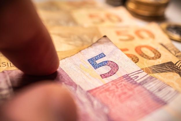 브라질 경제를 위한 근접 촬영 사진에서 5레알 지폐를 들고 있는 남자