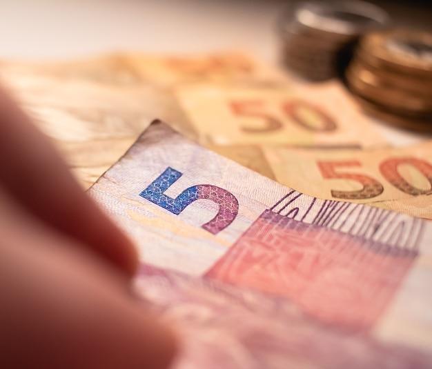 Мужчина держит банкноту в 5 реалов на снимке крупным планом для бразильской экономики
