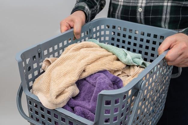 タオルがいっぱい入ったかごを持った男。