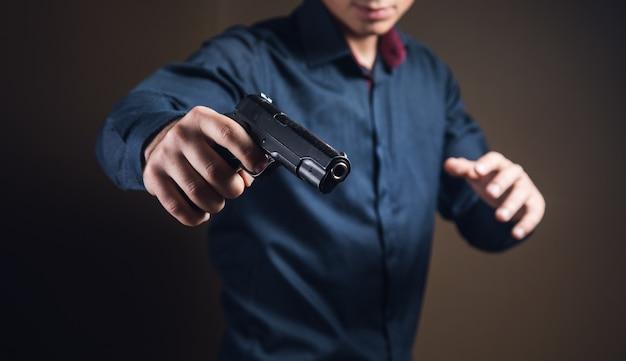 黒いピストルを手に持って威する男性 Premium写真