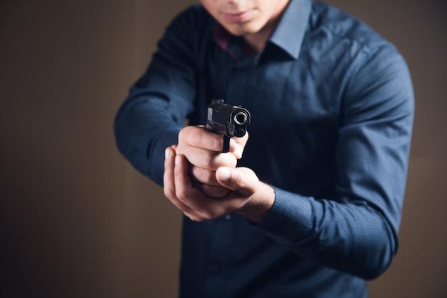 Мужчина держит в руке черный пистолет, угрожая