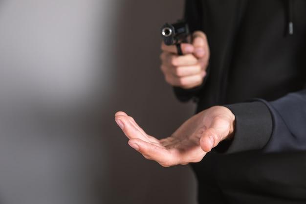 위협하는 그의 손에 검은 권총을 들고 남자