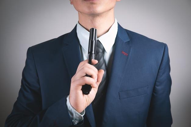 脅迫する手に黒いピストルを持っている男