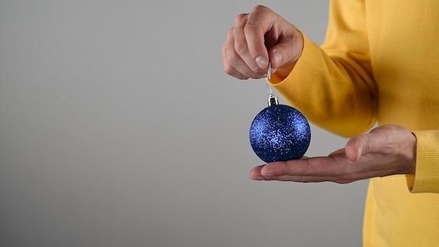 Мужчина держит в руке синий елочный шар.