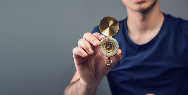 Мужчина держит компас в комнате
