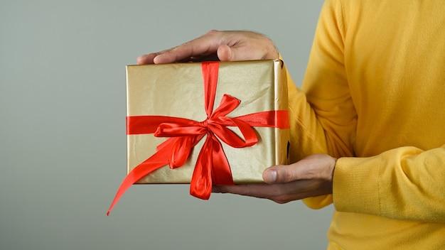 Мужчина держит подарочную коробку с красным бантом.