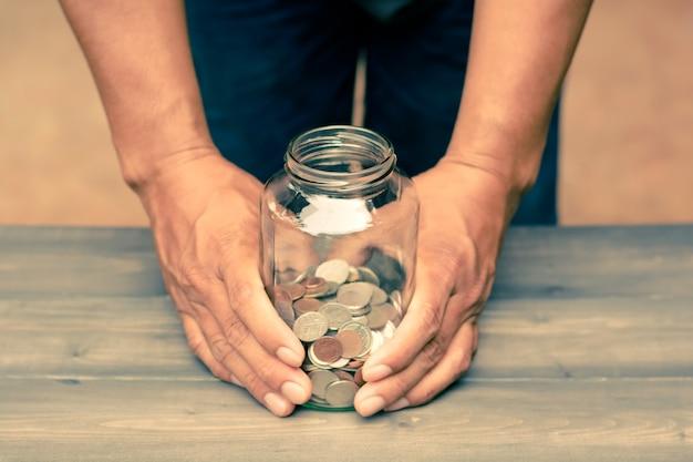Мужчина, держащий стеклянную банку, которые являются деньгами для экономии на деревянном столе