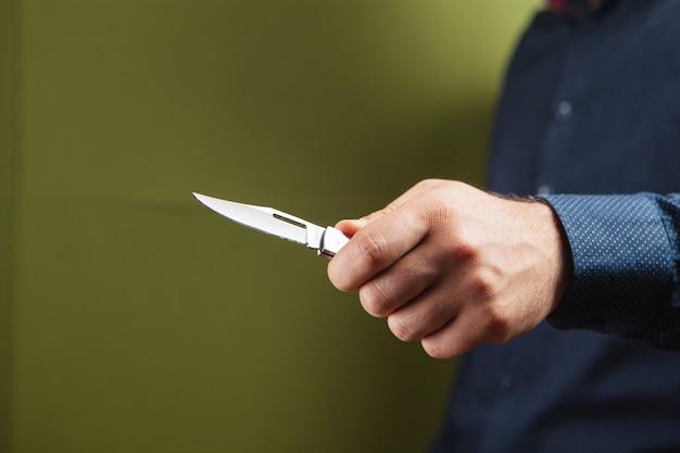 Мужчина держит ручной нож на зеленом фоне
