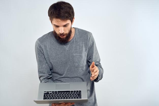 ノートパソコンのインターネット通信ライフスタイルテクノロジーライトスタジオを持っている男性。
