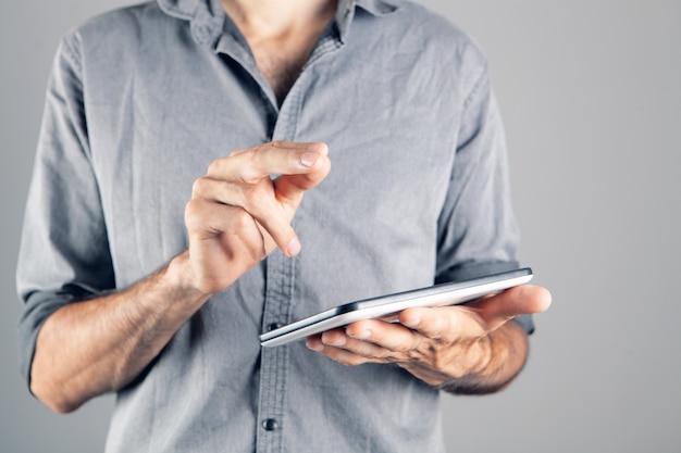 Мужчина держит планшет в руке