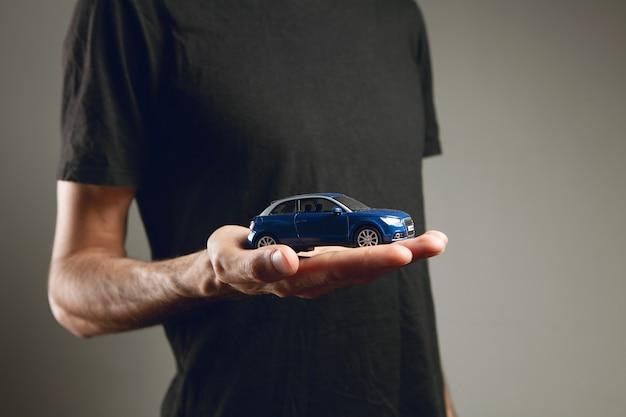 그의 손에 장난감 자동차를 들고 남자