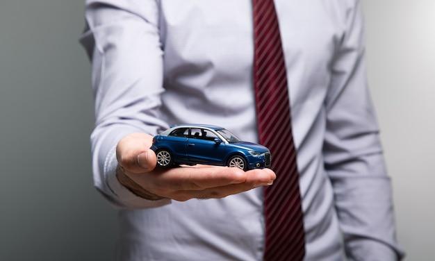 그의 손에 장난감 자동차를 들고 남자.