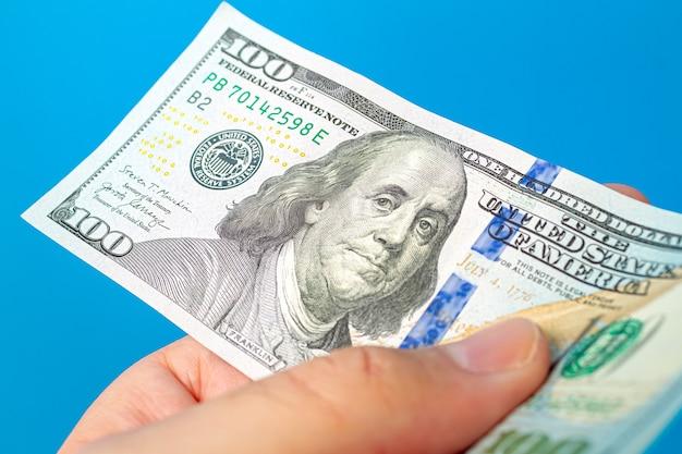 Мужчина держит пачку долларовых купюр на белом фоне