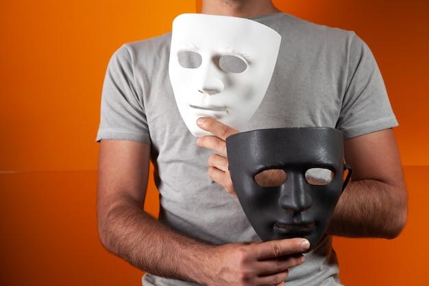 オレンジ色の背景に白と黒の匿名マスクを保持している男