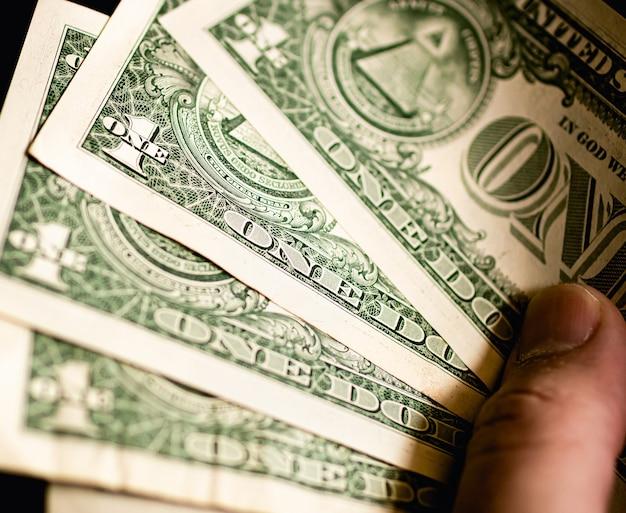 Мужчина держит долларовые банкноты сша в форме веера в темноте