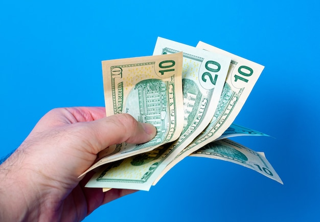 青い背景で私たちのドル紙幣を扇形に持っている男