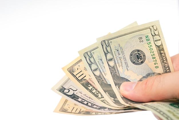 흰색 배경에 부채꼴 모양의 미국 달러 지폐를 들고 있는 남자
