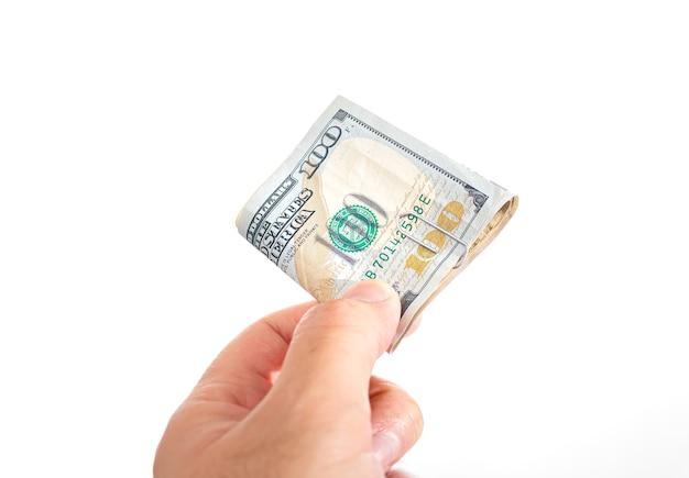 흰색 배경에 접힌 미국 달러 지폐를 들고 있는 남자