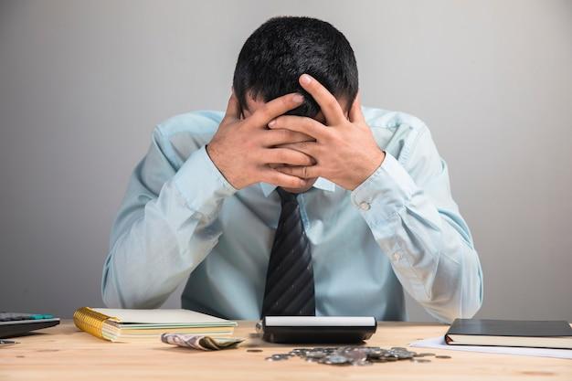 デスクトップの手で頭を抱えている男
