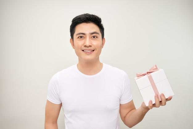 白い背景の上のプレゼントボックスを保持している男。