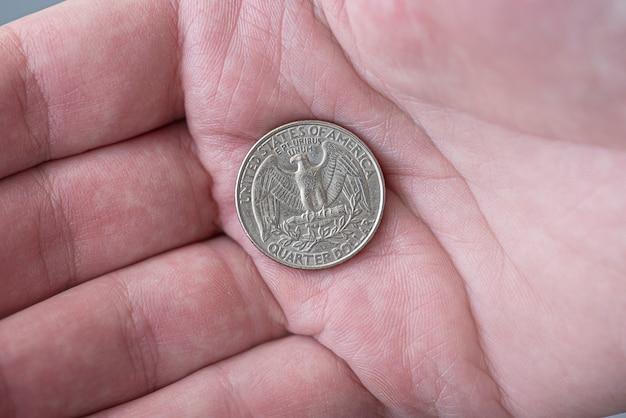 Мужчина держит серебряную американскую четверть долларовую монету, 25 центов, сша