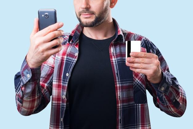 男は手に銀行カードとスマートフォンを持っています