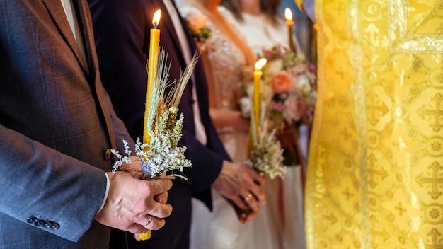 男はろうそくを持っており、正教会の司祭が教会で奉仕しています。結婚式