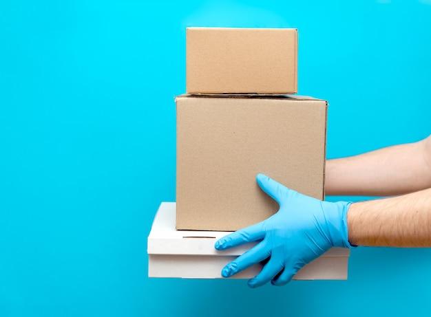 한 남자가 고무 장갑에 손으로 골판지 상자를 들고 있습니다. covid-19에 대한 보호. 코로나 바이러스가 유행하는 동안 물품의 안전한 배송.